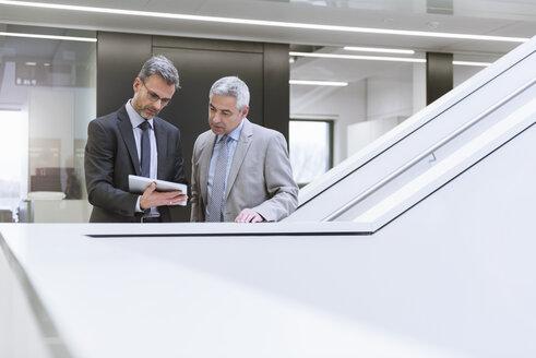 Two businessmen having an informal meeting, using digital tablet - DIGF01565