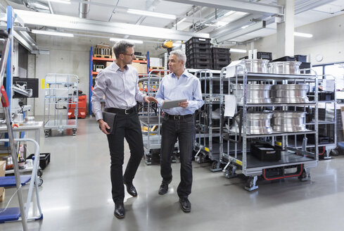 Two businessmen walking in factory hall - DIGF01586