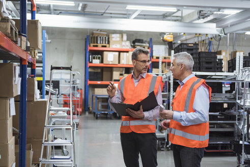Two colleagues in factory hall wearing safety vests holding clipboard - DIGF01589