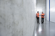 Two colleagues wearing safety vests talking - DIGF01598