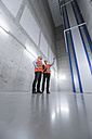 Two colleagues wearing safety vests and hard hats talking in a building - DIGF01601