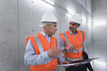 Two colleagues wearing safety vests and hard hats talking in a building - DIGF01604