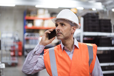 Man in factory hall wearing safety vest and hard hat talking on cell phone - DIGF01607