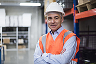 Portrait of man in factory hall wearing safety vest and hard hat - DIGF01610