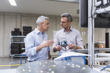 Two businessmen in factory hall examining product - DIGF01619