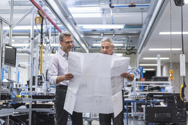 Two businessmen in factory hall discussing construction plan - DIGF01622