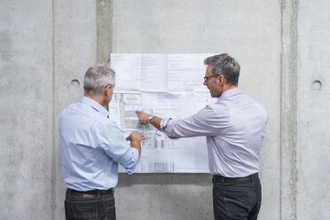 Two businessmen discussing construction plan at concrete wall - DIGF01625