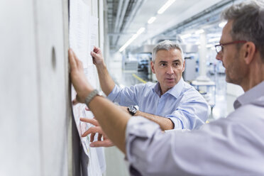 Two businessmen discussing construction plan at concrete wall - DIGF01628