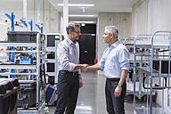 Two businessmen shaking hands in factory hall - DIGF01631