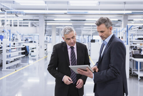 Two mangagers having a meeting at the shop floor of a factory - DIGF01634