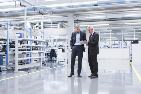 Two mangagers having a meeting at the shop floor of a factory - DIGF01643