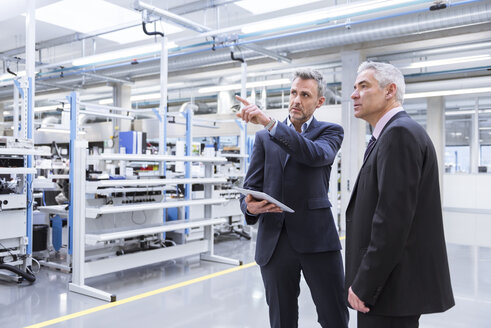 Two mangagers having a meeting at the shop floor of a factory - DIGF01649