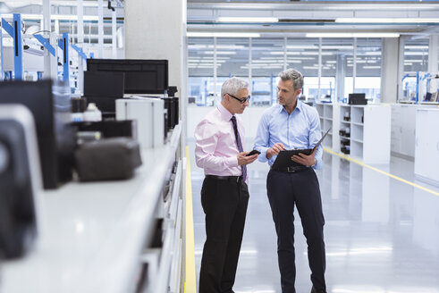 Two mangers discussing on shop floor of company - DIGF01658