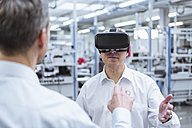 Two managers standing in company, using VR goggles - DIGF01700