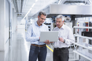 Two managers standing in company using laptop - DIGF01709