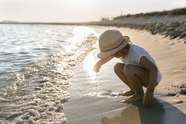 Spain, Menorca, little girl playing on the beach - MGOF03158
