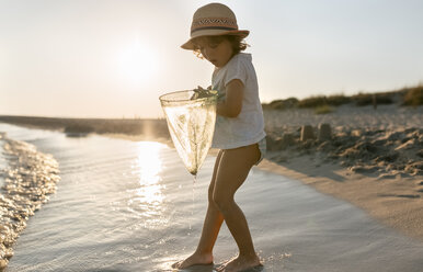 Spain, Menorca, little girl with a dip net on the beach - MGOF03164
