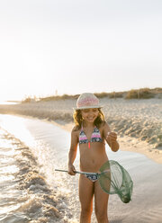 Spain, Menorca, happy girl with a dip net on the beach - MGOF03170