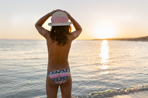 Spain, Menorca, girl watching the sunset on the beach - MGOF03173