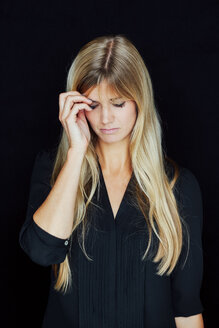 Portrait of suffering blond woman in front of black background - CHAF01803