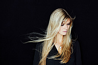Portrait of young blond woman with blowing hair in front of black background - CHAF01806