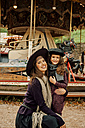 Portrait of smiling young woman and little girl in front of children's carousel at fair - CHAF01809