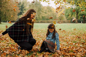 Young woman and little girl playing with autumn leaves on a meadow - CHAF01812