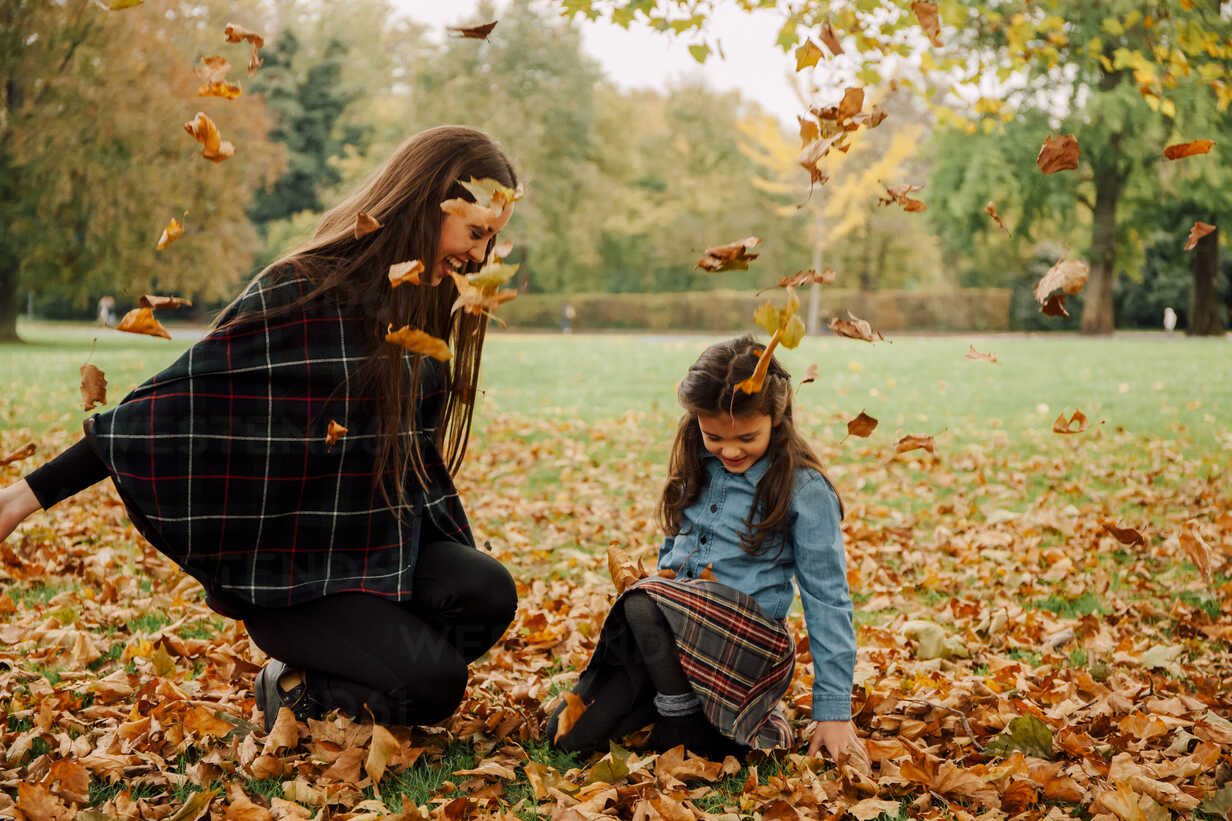 Young woman and little girl playing with autumn leaves on a meadow - CHAF01812 - Chris Adams/Westend61