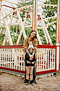 Young woman and little girl standing in front of swing at fair - CHAF01815
