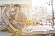 Happy couple sitting on rooftop, embracing each other - WESTF22829