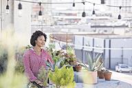Smiling woman standing in her rooftop garden - WESTF22832