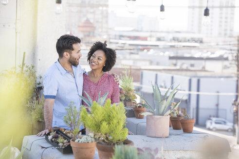 Couple standing in their rooftop garden - WESTF22835