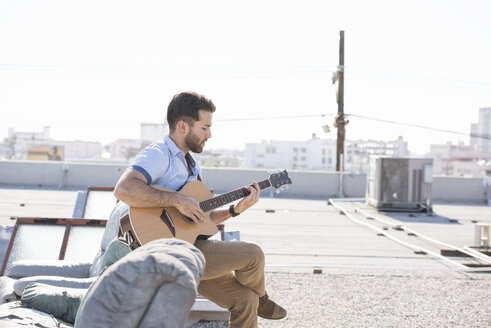 Young man on rooftop sitting on sofa and playing guitar - WESTF22838
