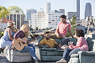 Friends having a rooftop party and playing guitar - WESTF22862