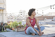 Young woman sitting on rooftop terrace, enjoying the sun - WESTF22877