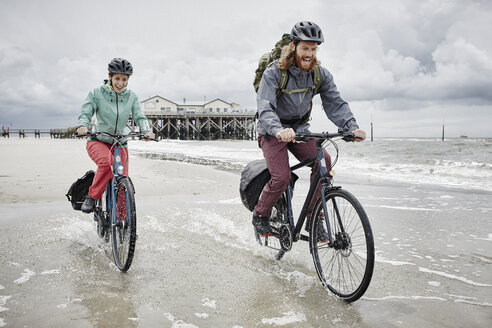 Germany, Schleswig-Holstein, St Peter-Ording, happy couple riding bicycle on the beach - RORF00713