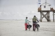 Germany, Schleswig-Holstein, St Peter-Ording, couple pushing bicycles on the beach - RORF00716
