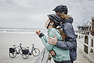 Germany, Schleswig-Holstein, St Peter-Ording, couple on a bicycle trip having a break on jetty at the beach - RORF00722