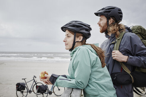 Germany, Schleswig-Holstein, St Peter-Ording, couple on a bicycle trip having a break on jetty at the beach - RORF00725