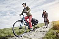 Germany, Schleswig-Holstein, Eiderstedt, couple riding bicycle through salt marsh - RORF00734