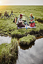 Germany, Schleswig-Holstein, Eiderstedt, couple with bicycles camping in marsh landscape - RORF00737