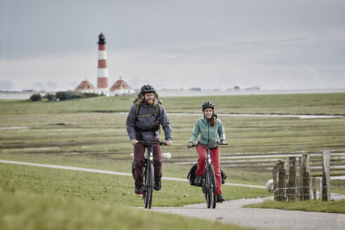 Germany, Schleswig-Holstein, Eiderstedt, couple riding bicycle near Westerheversand Lighthouse - RORF00743
