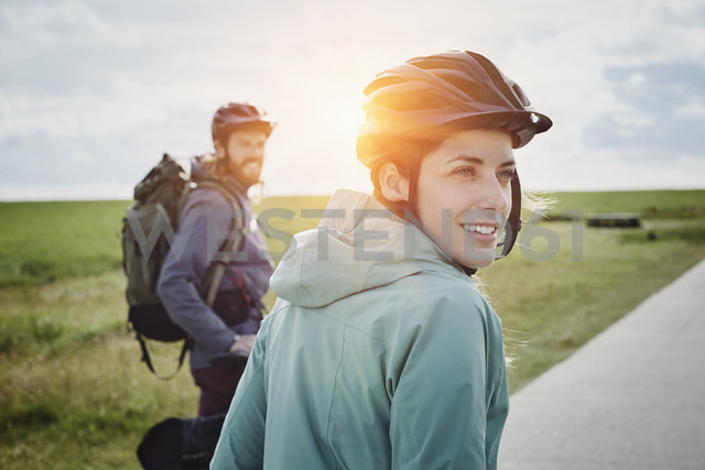 Germany, Schleswig-Holstein, Eiderstedt, couple on a bicycle tour having a break in marsh landscape - RORF00746