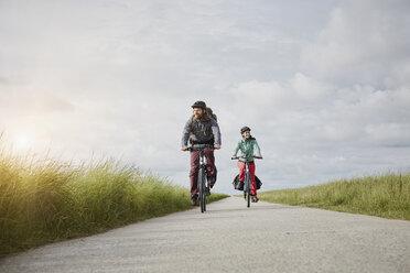 Germany, Schleswig-Holstein, Eiderstedt, couple riding bicycle on path through salt marsh - RORF00749