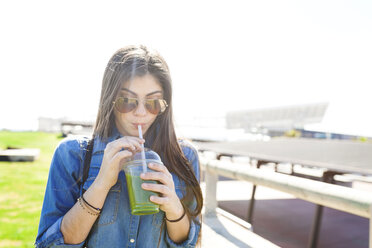 Spain, Barcelona, young woman drinking green beverage - VABF01269