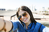Portrait of smiling young woman wearing sunglasses taking selfie - VABF01272