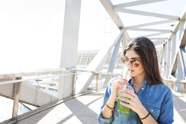 Spain, Barcelona, young woman with beverage on a bridge - VABF01275
