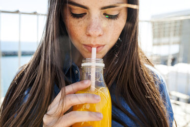 Young woman with freckles drinking orange juice - VABF01281