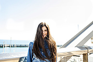 Smiling young woman with long brown hair standing on bridge - VABF01284