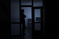 Man standing in office at night - KNSF01193